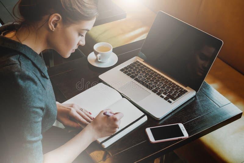 坐在咖啡馆的桌上和写在笔记本的灰色礼服的年轻女商人 免版税库存照片
