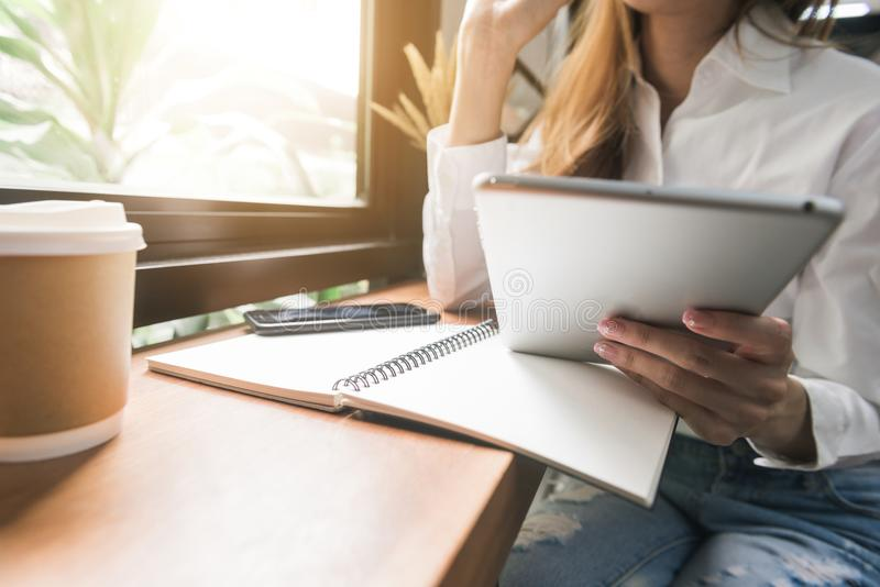 坐在咖啡馆的桌上和写在笔记本的白色礼服的年轻女商人 用片剂和咖啡的亚裔妇女 库存图片