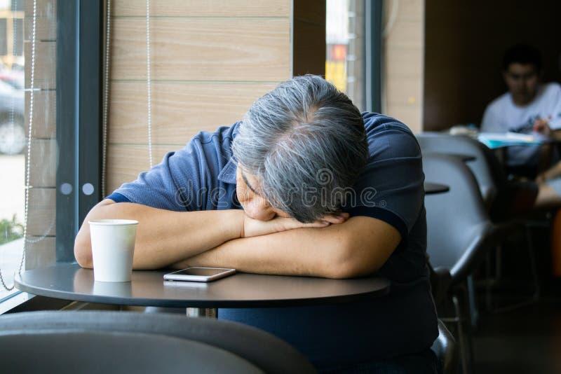 坐在咖啡馆的沮丧的中间年迈的人 库存图片