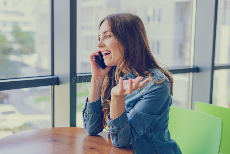 坐在咖啡馆的激动的笑的俏丽的妇女,她在电话谈话并且说闲话与她的最好的朋友 表达的情感加州 免版税库存图片