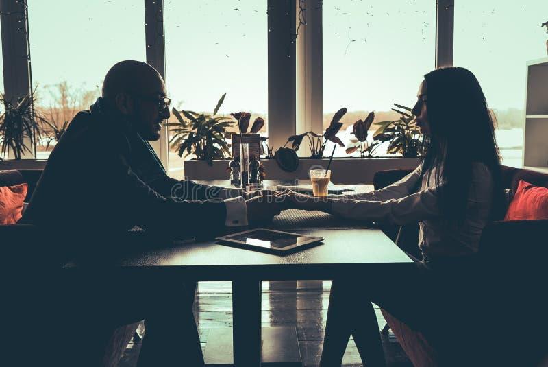 坐在咖啡馆的爱夫妇的剪影 库存照片
