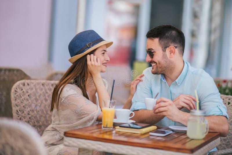 坐在咖啡馆的爱的夫妇享用在咖啡和交谈,选择聚焦 免版税库存照片