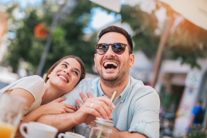坐在咖啡馆的爱的夫妇享用在咖啡和交谈 免版税库存照片