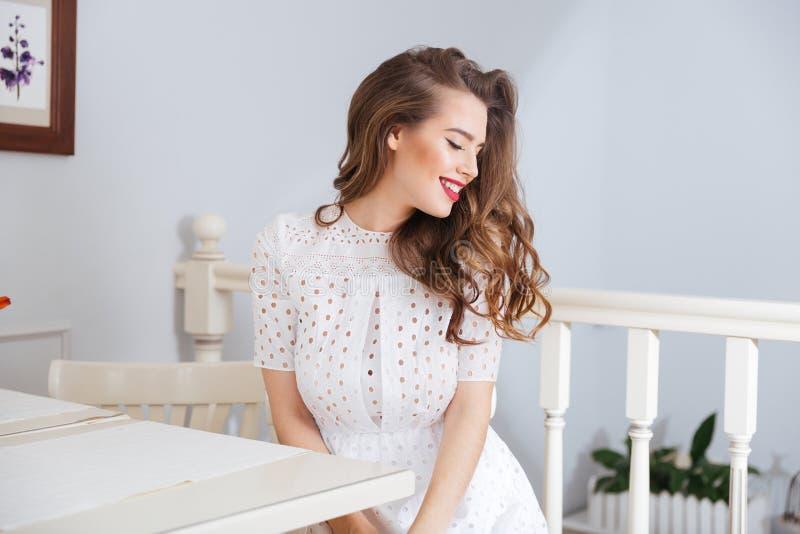 坐在咖啡馆的白色礼服的愉快的可爱的少妇 免版税库存照片