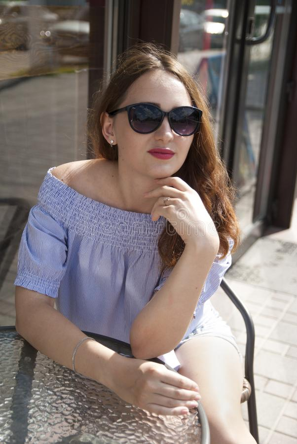 坐在咖啡馆的美丽的女孩 免版税库存图片