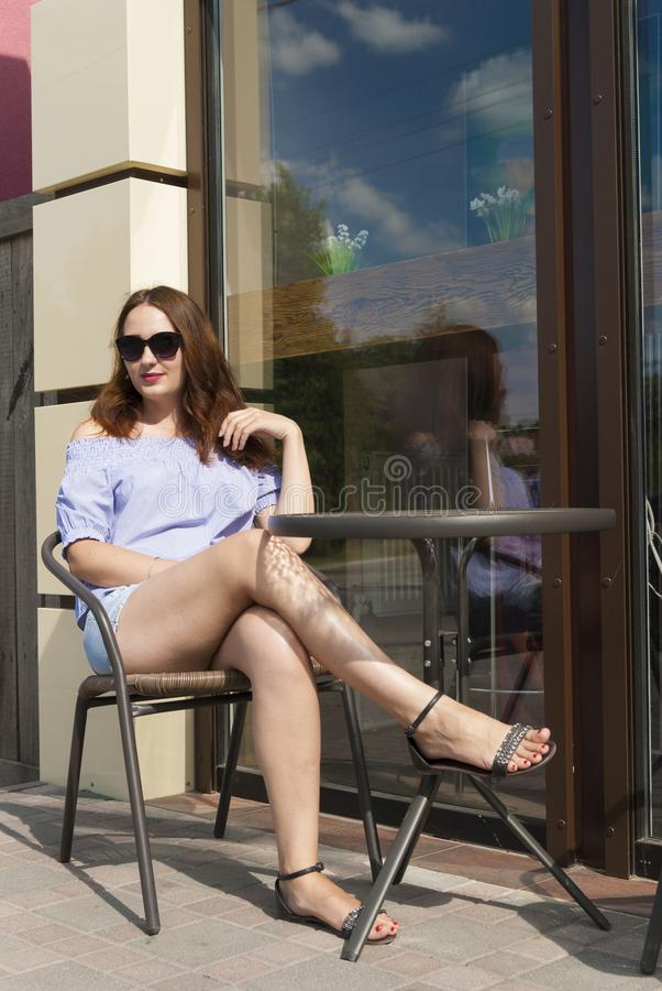 坐在咖啡馆的美丽的女孩 图库摄影