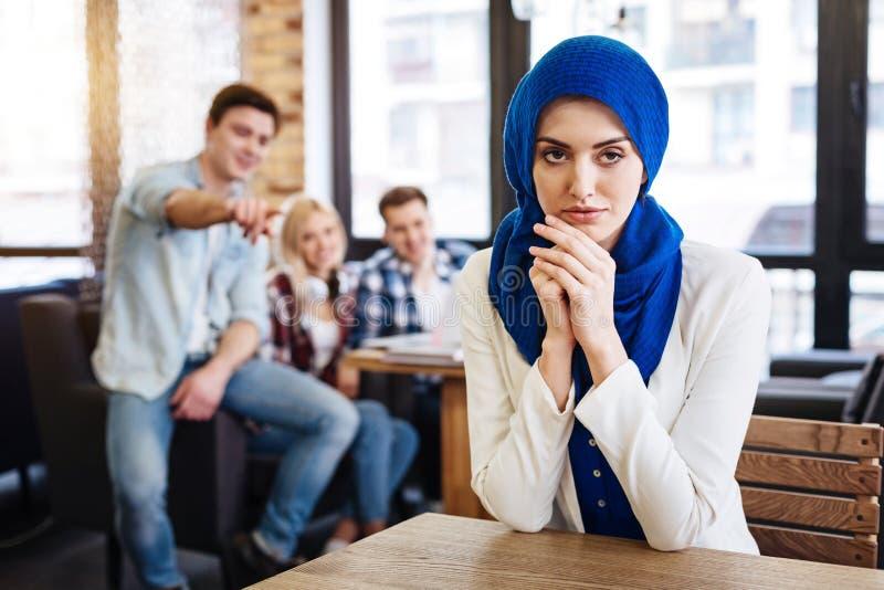 坐在咖啡馆的美丽的宜人的回教妇女 免版税库存照片