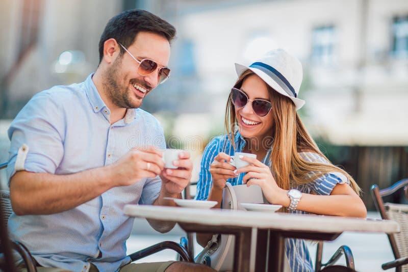 坐在咖啡馆的美好的爱恋的夫妇享用在咖啡 免版税库存照片