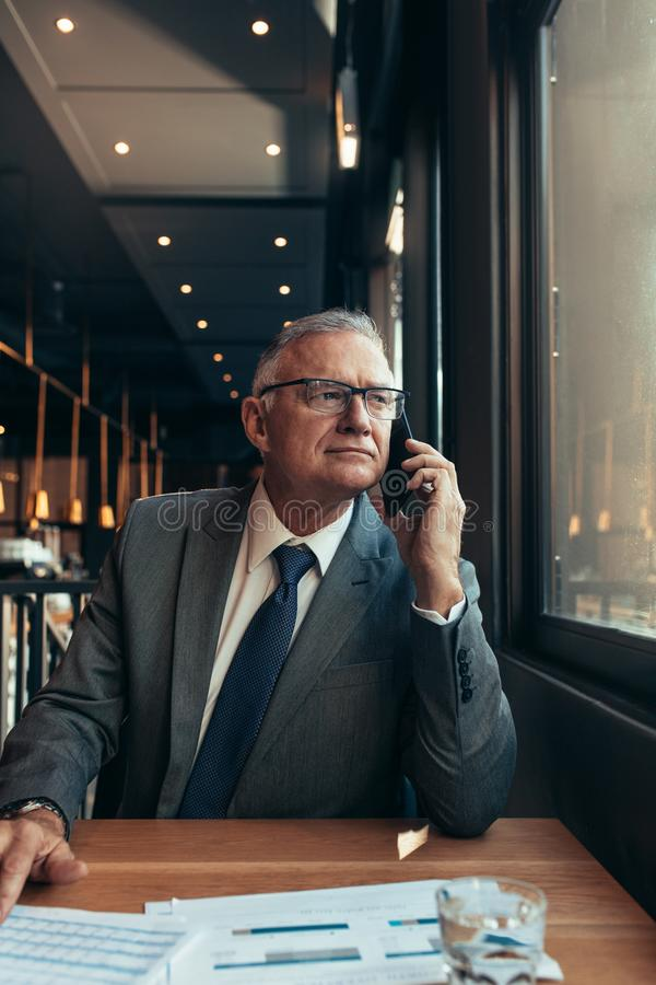 坐在咖啡馆的资深商人打电话 免版税库存图片