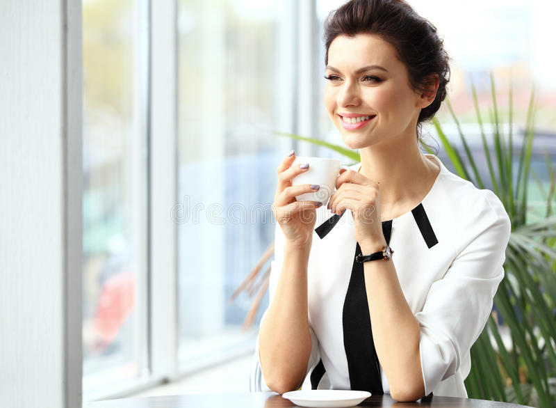 坐在咖啡馆的年轻专业女实业家 免版税库存照片