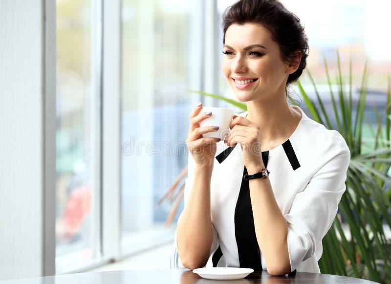 坐在咖啡馆的年轻专业女实业家 库存图片