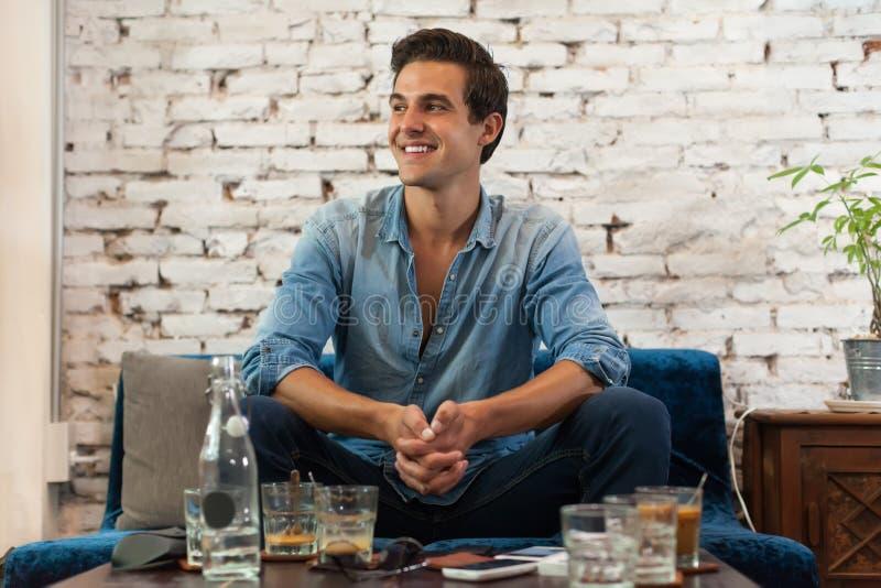 坐在咖啡馆表上的英俊的人微笑 库存图片