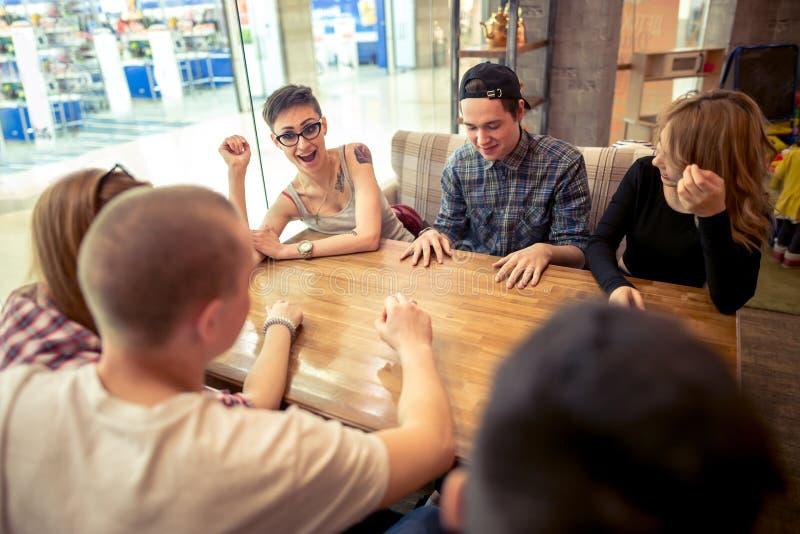 坐在咖啡馆酒吧的小组学生看彼此 免版税库存照片