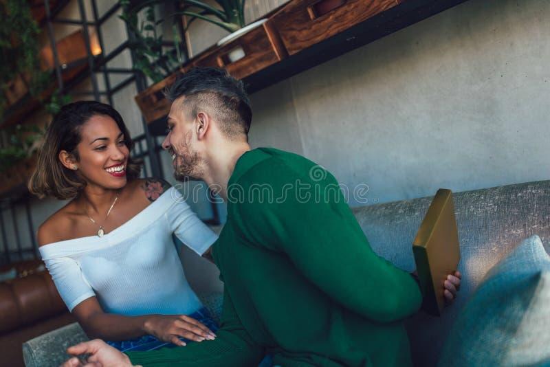 坐在咖啡馆酒吧的愉快的人种间夫妇 库存图片
