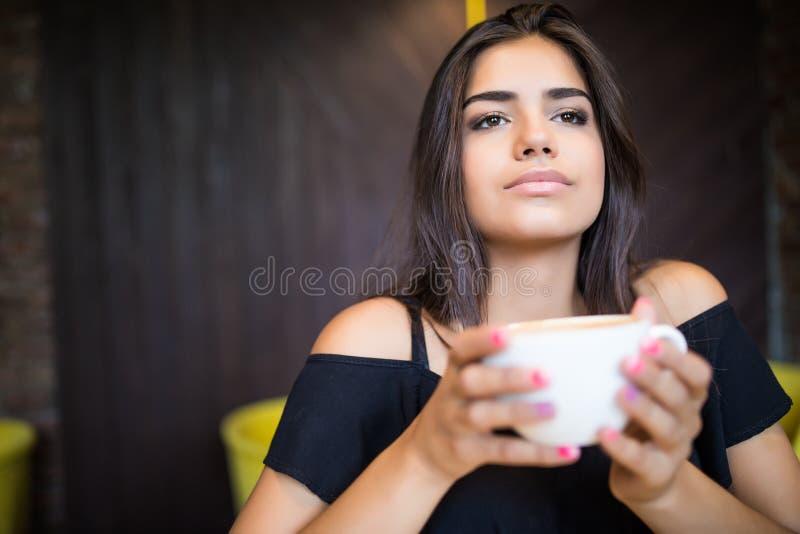 坐在咖啡馆饮用的咖啡的年轻美丽的妇女画象  图库摄影