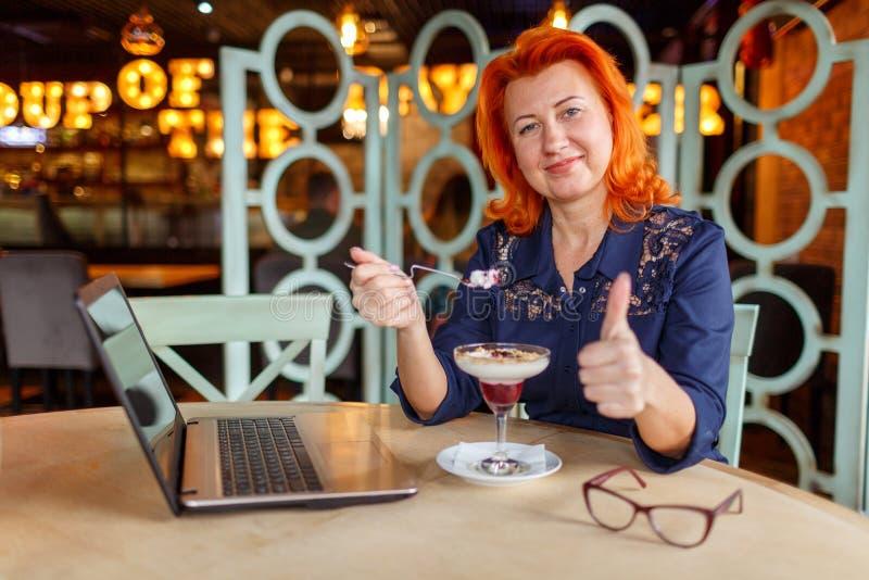 坐在咖啡馆,吃点心和显示反馈赞许的妇女 库存图片