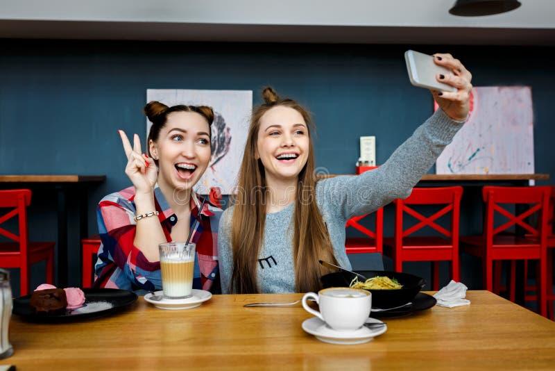 坐在咖啡馆,时髦的时髦成套装备,欧洲假期,街道样式的两名年轻美丽的行家妇女,愉快,有 库存照片
