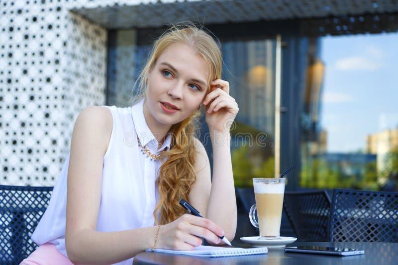 坐在咖啡馆,饮用的咖啡和做在笔记本的年轻女人笔记 库存照片