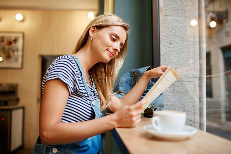 坐在咖啡馆读书杂志a的美丽的年轻怀孕的女孩 免版税库存照片