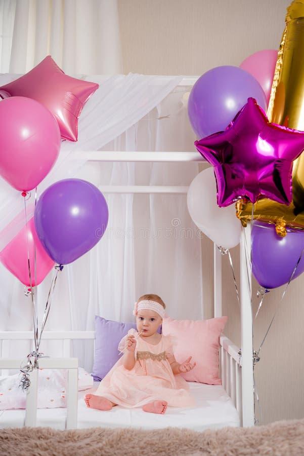 坐在咬住从气球的生日礼服的一张床上的美丽的小女孩一支鞭子 图库摄影