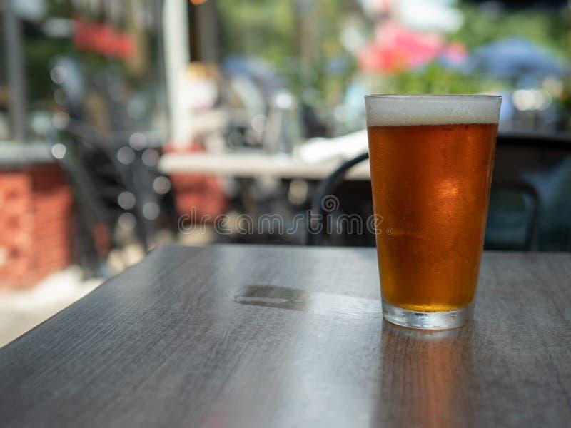 坐在品脱玻璃的冰冷的琥珀色的啤酒在桌外面与湿杯子圆环 免版税图库摄影