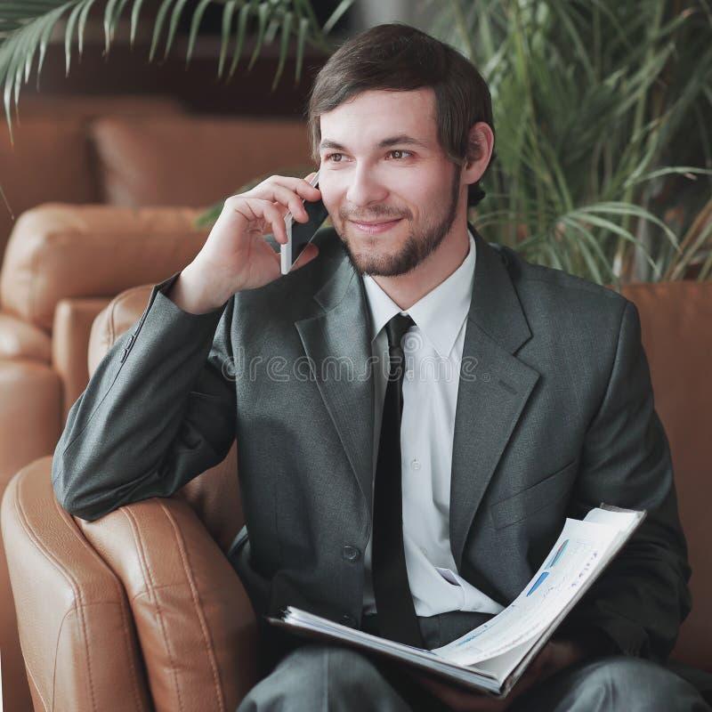 ?? 坐在商业中心的商人读文件,当有电话时 免版税库存图片