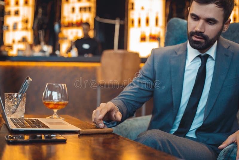 坐在商业中心酒吧饮用的威士忌酒的商人得到雪茄 库存照片