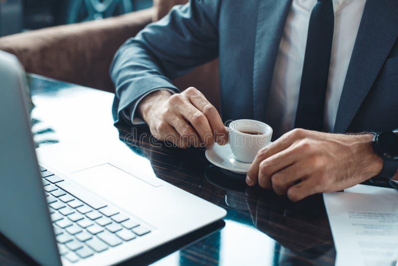 坐在商业中心餐馆srinking的浓咖啡特写镜头的商人 免版税库存照片