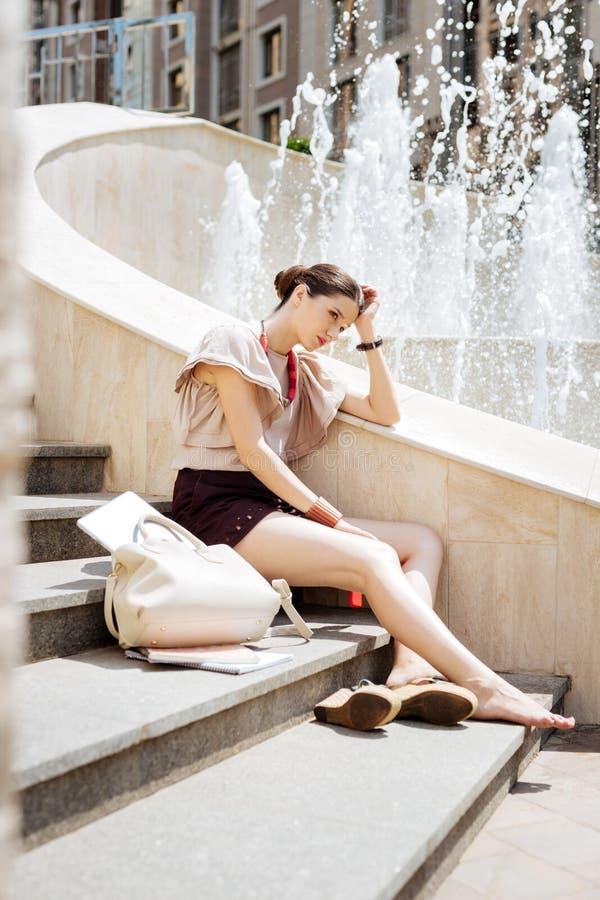 坐在喷泉附近的宜人的少妇 库存图片