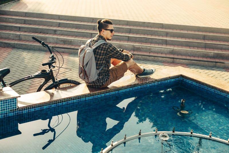 坐在喷泉附近的年轻人骑自行车者在夏天公园每日生活方式都市休息的概念的自行车旁边 免版税库存照片