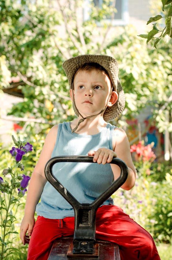 坐在国家庭院里的体贴的年轻男孩 图库摄影