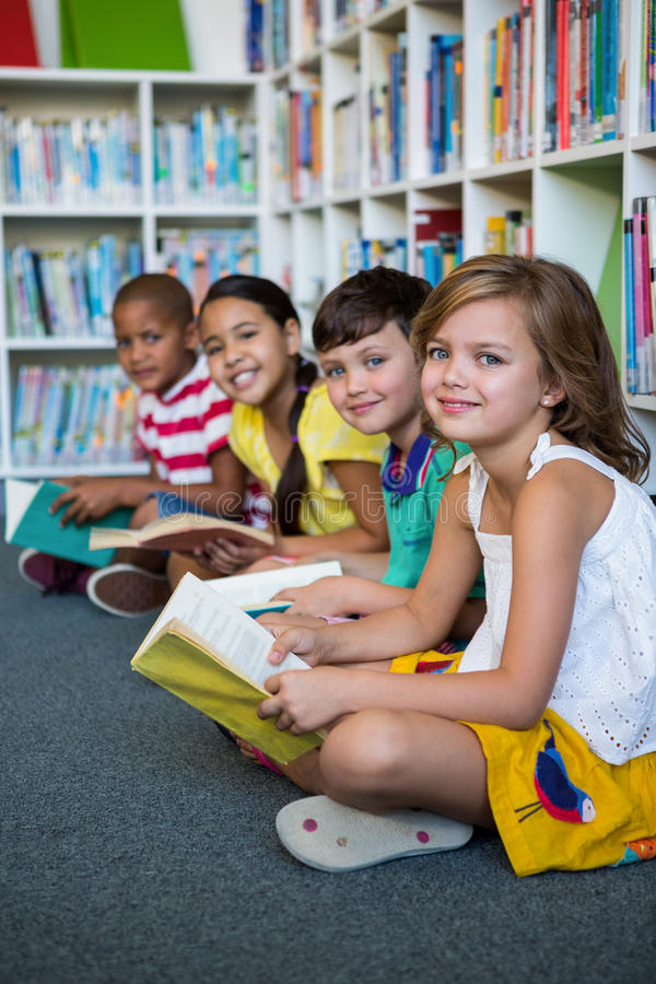 坐在图书馆的微笑的学生在学校 库存图片