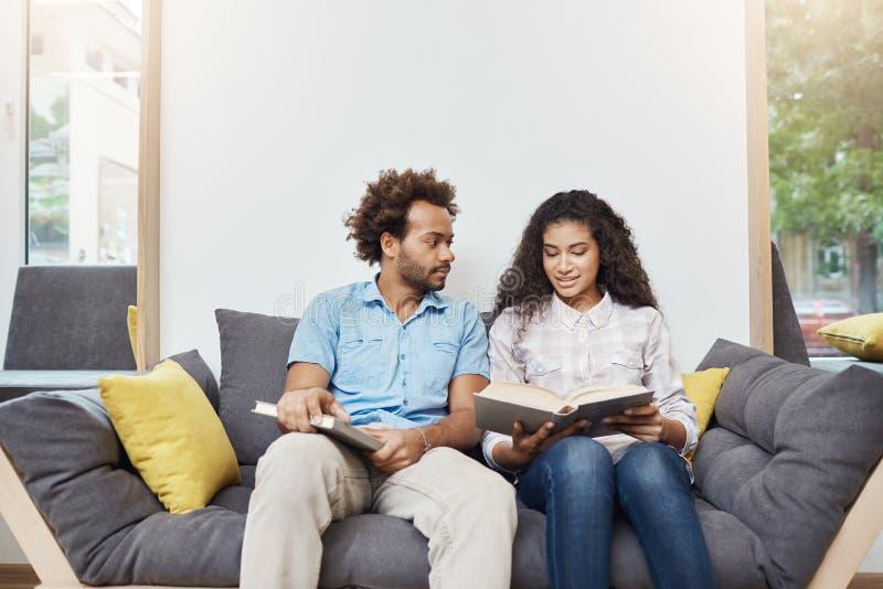 坐在图书馆里的对美丽的黑皮肤的年轻学生在研究以后,读关于历史的信息 免版税库存图片