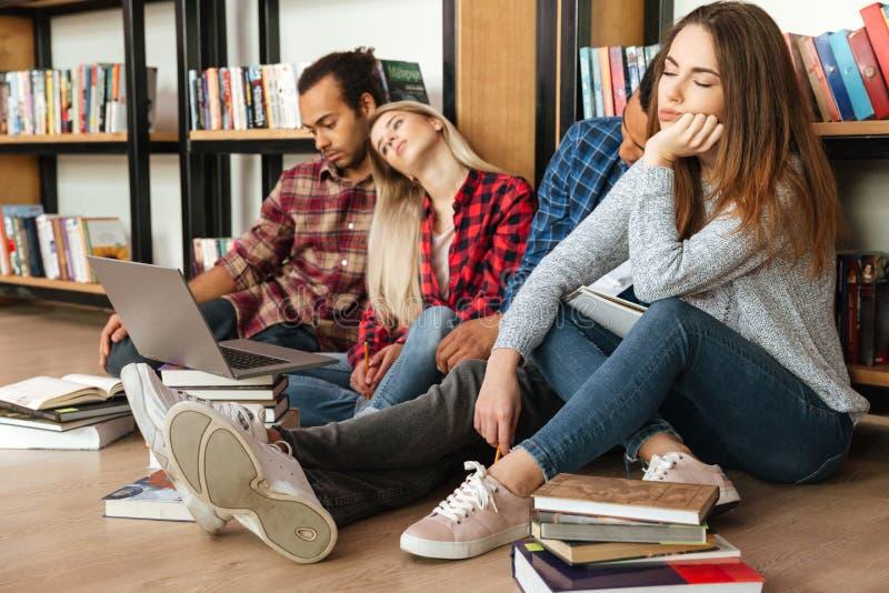 坐在图书馆里的疲乏的学生在地板使用便携式计算机 免版税库存照片