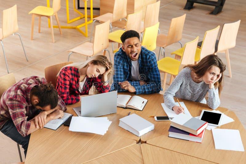 坐在图书馆里的疲乏的学生 库存照片