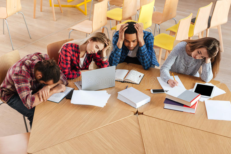 坐在图书馆里的疲乏的学生 库存图片