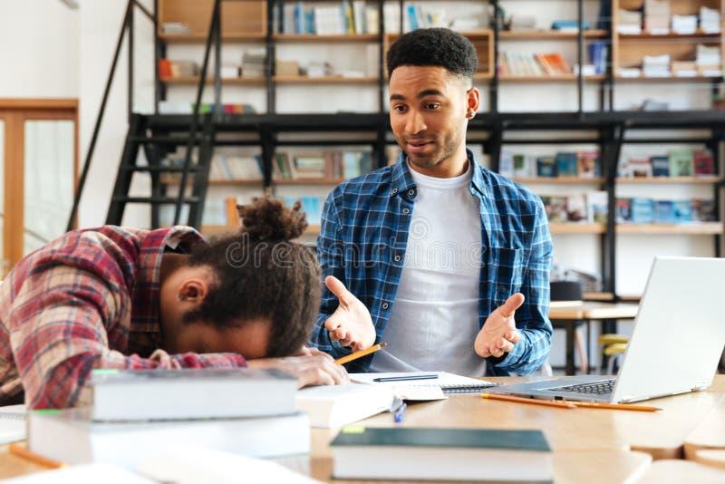 坐在图书馆里的年轻疲乏的非洲人学生 免版税库存图片
