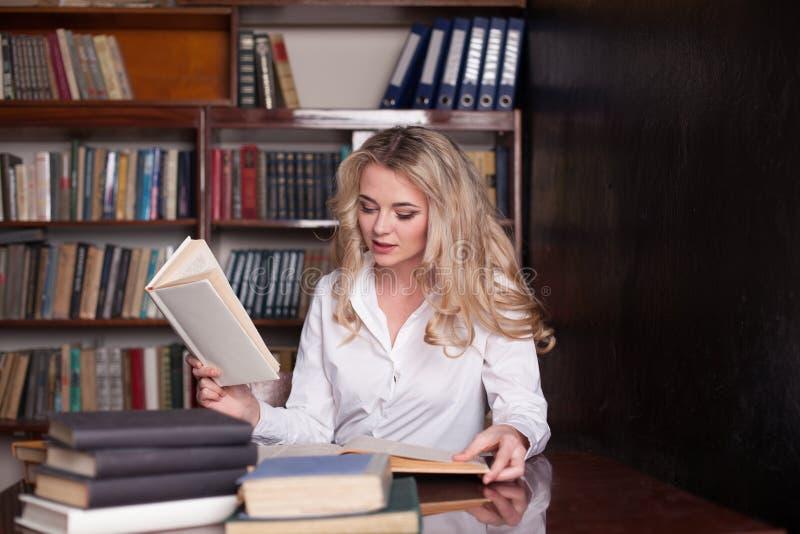 坐在图书馆阅读书的女孩为检查做准备 库存照片
