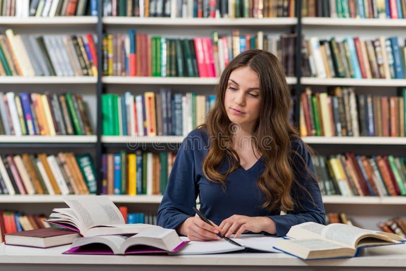 坐在图书馆wi的一张书桌的一个年轻深色的女孩 免版税图库摄影