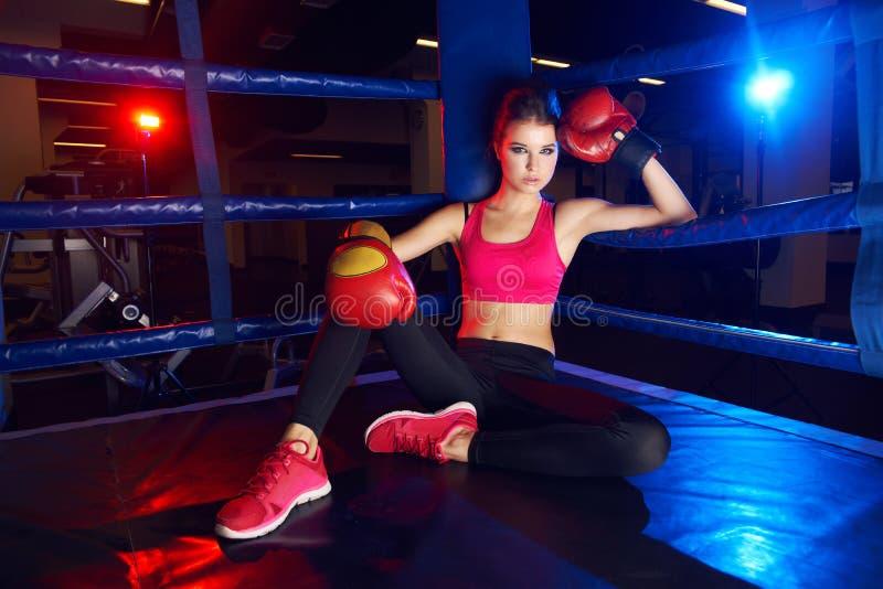 坐在圆环角落的拳击手妇女充分的身体画象 免版税库存图片