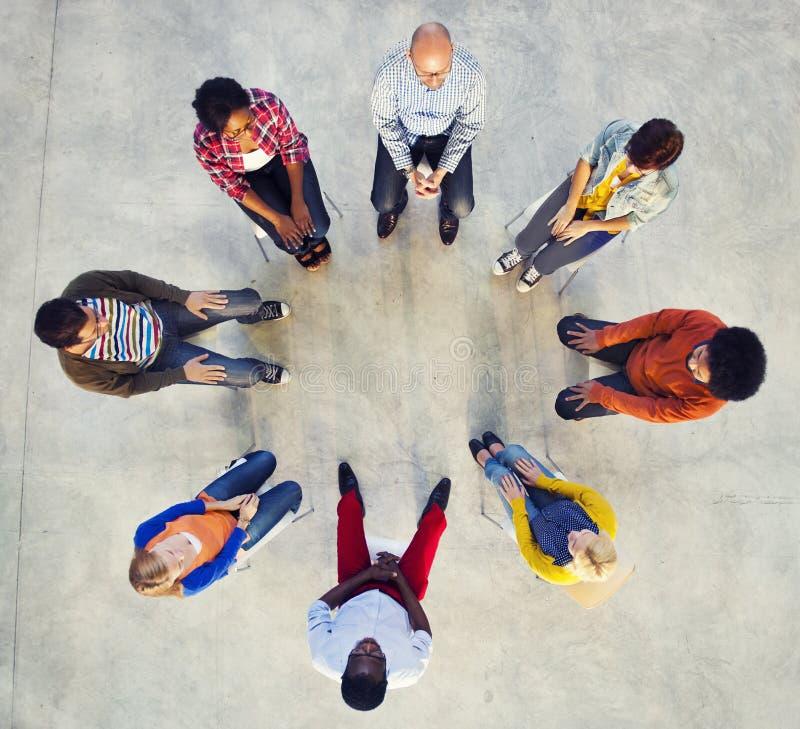 坐在圈子的不同种族的人 库存照片