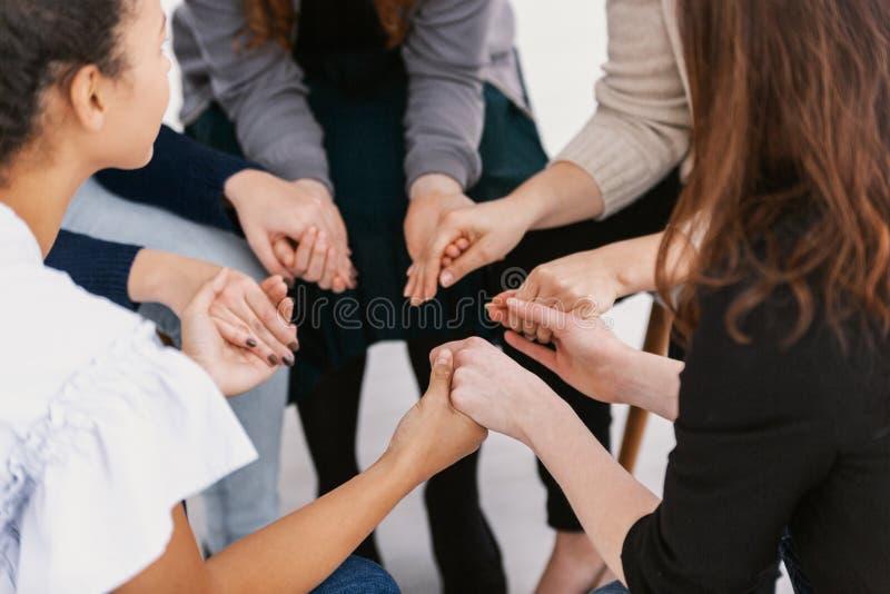 坐在圈子的小组女性握手在支持小组聚会期间 库存照片