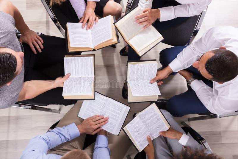 坐在圈子读书圣经的人们 库存图片