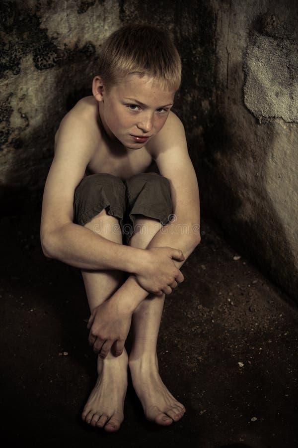 坐在土牢的被监禁的男孩 库存图片