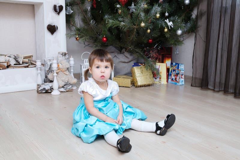 坐在圣诞树下的小女孩 图库摄影