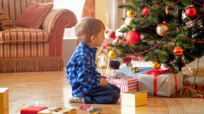 坐在圣诞树下的逗人喜爱的小男孩在早晨 免版税图库摄影