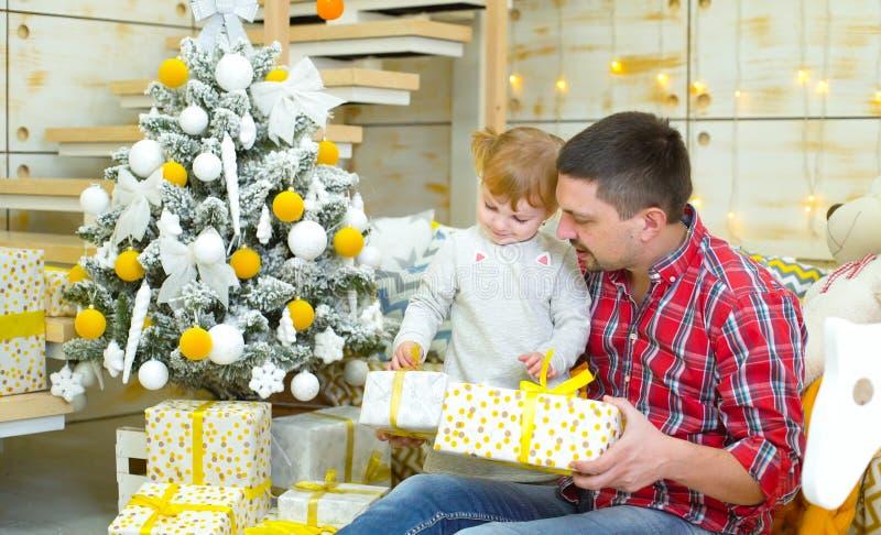 坐在圣诞树和打开的礼物盒附近的年轻父亲和小孩女儿 库存图片
