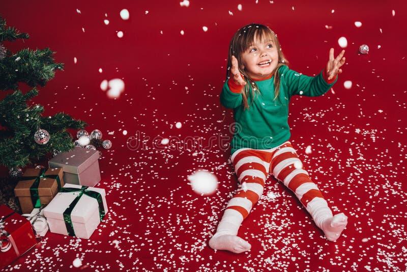 坐在圣诞树旁边的孩子享受人为降雪 库存照片
