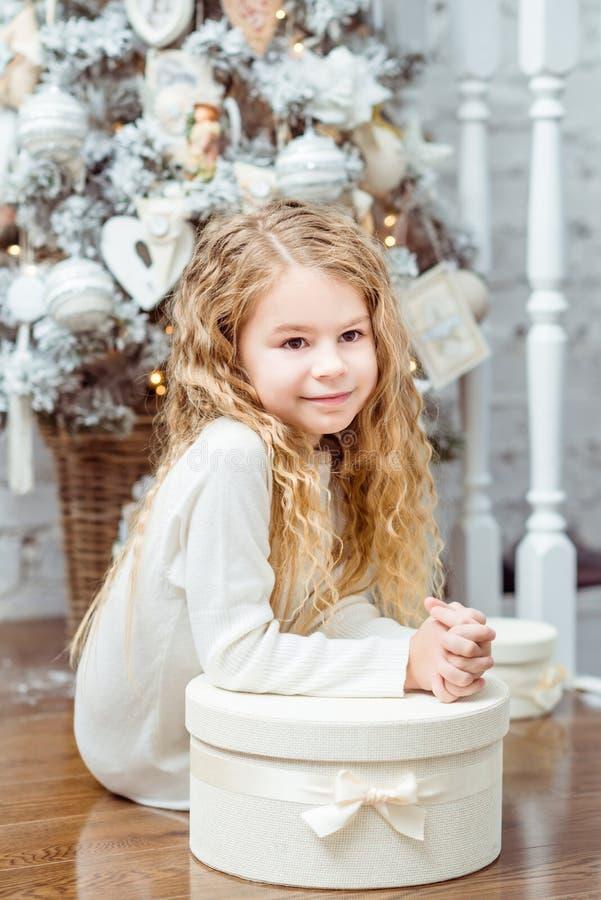坐在圣诞树机智下的美丽的白肤金发的小女孩 免版税图库摄影
