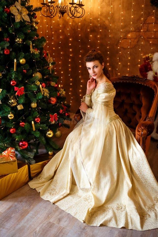 坐在圣诞树的一件美丽的礼服的美丽的少妇与礼物、圣诞节和新年 免版税图库摄影